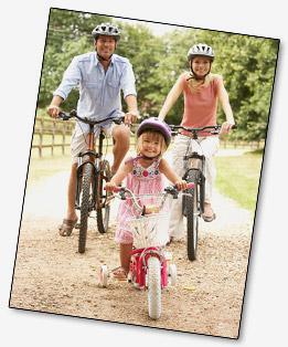 photo of young family safetly biking on a trail